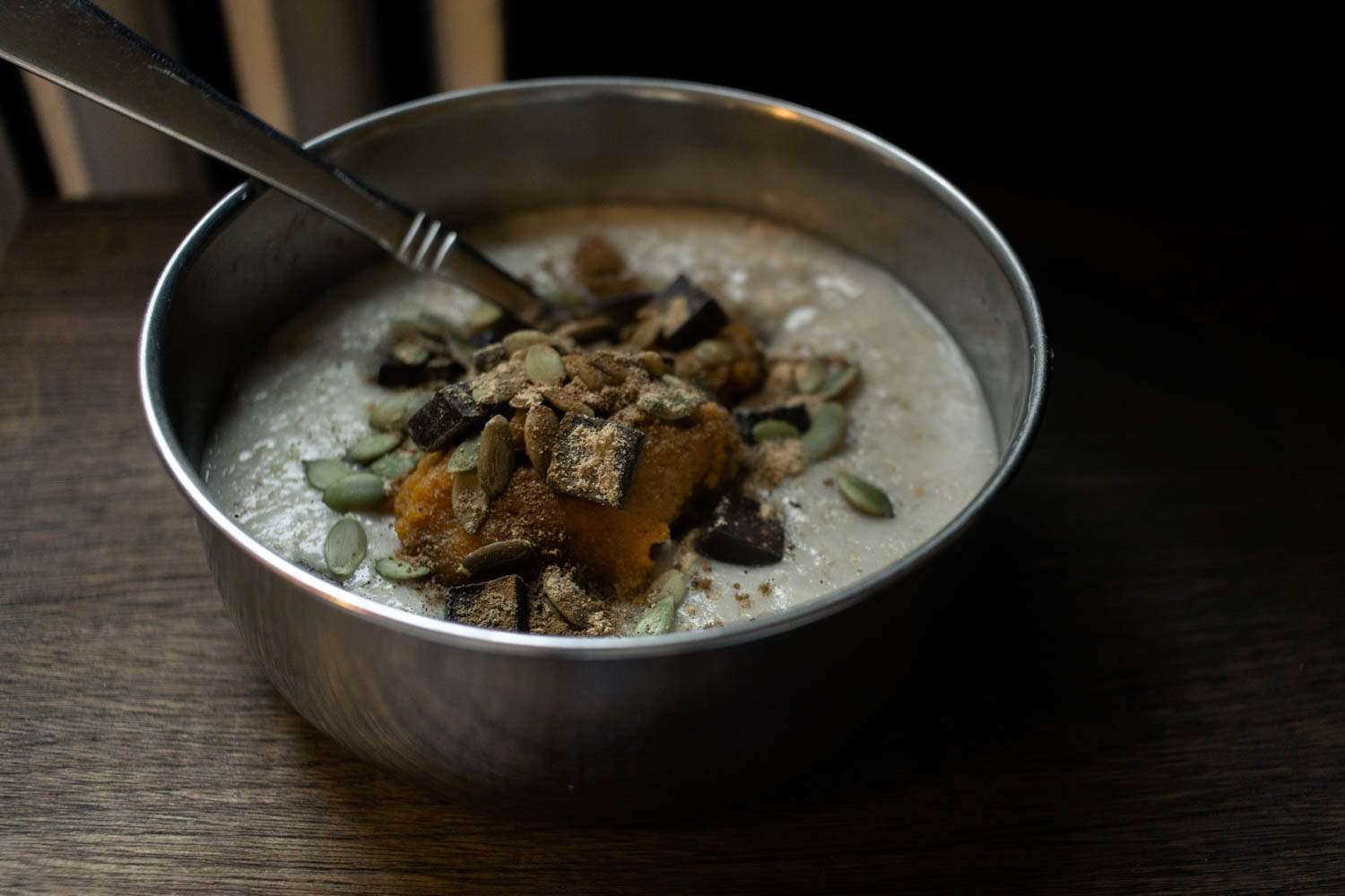 Steel-cut oats with pumpkin, spices and chocolate in a metal bowl
